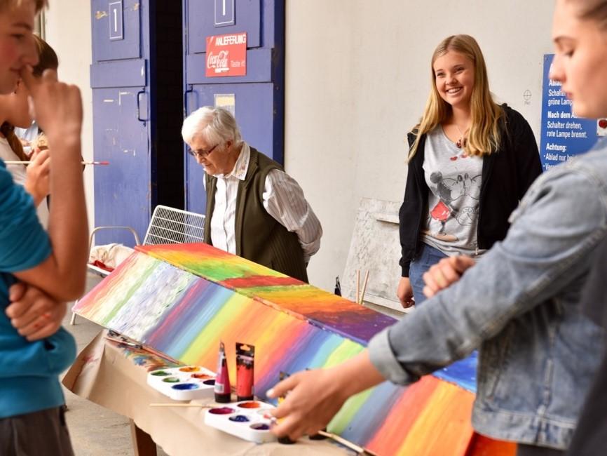 Ali Tschanz betrachtet das bald fertige Werk. Der Regenbogenverlauf gefällt der Seniorin. «Da kann ich mich ja drauf freuen», sagt sie lachend. (Foto: Daniela Friedli)